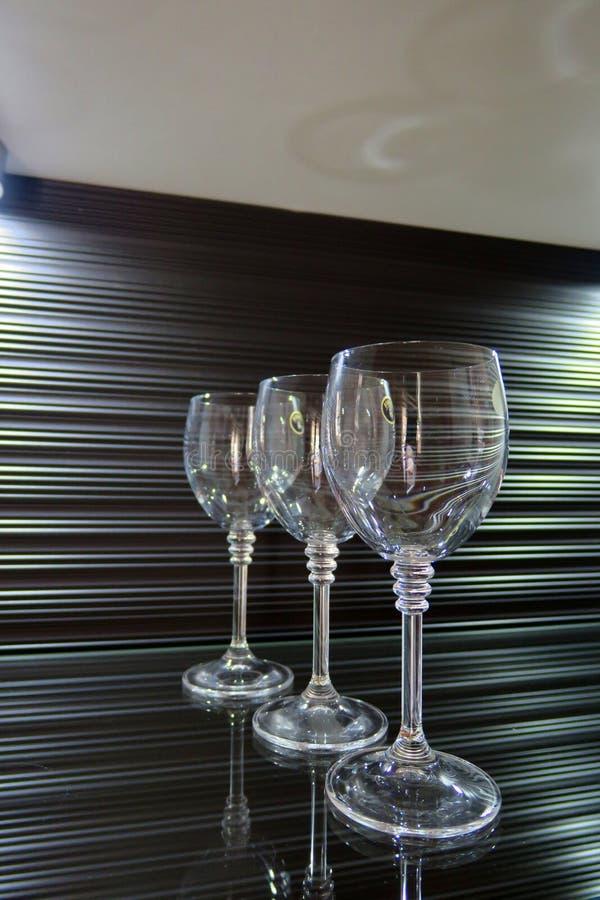 Trois hauts verres transparents sur un beau fond brun photographie stock