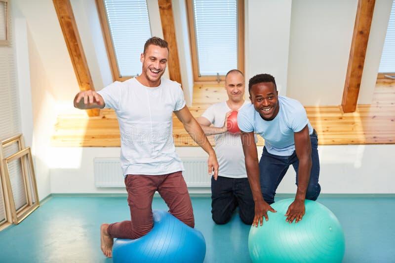 Trois hommes avec la boule de stabilité ont l'amusement image stock