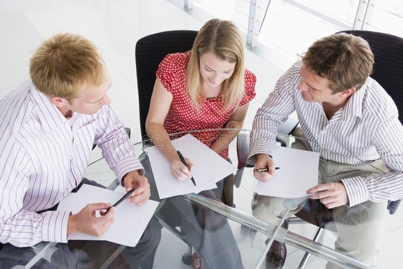 Trois hommes d'affaires dans la salle de réunion avec des écritures images stock