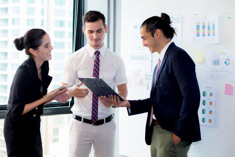 Trois hommes d'affaires se tenant dans le bureau moderne regardant le document de dossier et parlant dans le lieu de réunion images stock