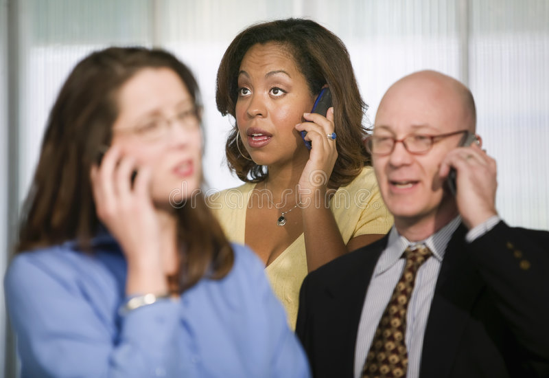 Trois hommes d'affaires sur des téléphones portables photo libre de droits