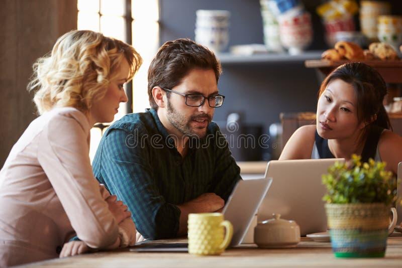 Trois hommes d'affaires travaillant à l'ordinateur portable en café photographie stock