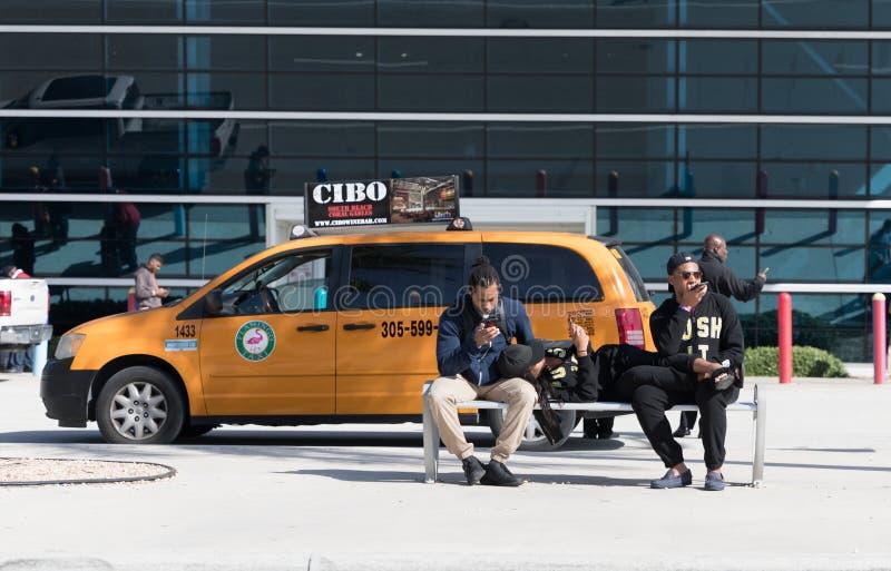 Trois hommes dans la chaise regardant le téléphone portable dans leurs propres mains images libres de droits
