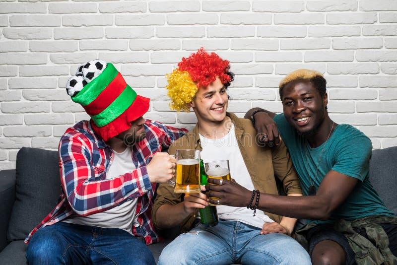 Trois hommes heureux s'asseyant sur le divan et le sport de observation sur la TV et la bière d'acclamations photos libres de droits