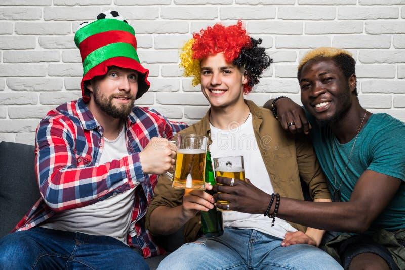 Trois hommes heureux s'asseyant sur le divan et le sport de observation sur la TV et la bière d'acclamations image libre de droits
