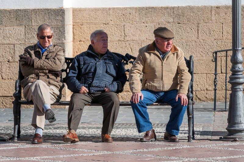 Trois hommes supérieurs s'asseyent sur un banc photographie stock libre de droits