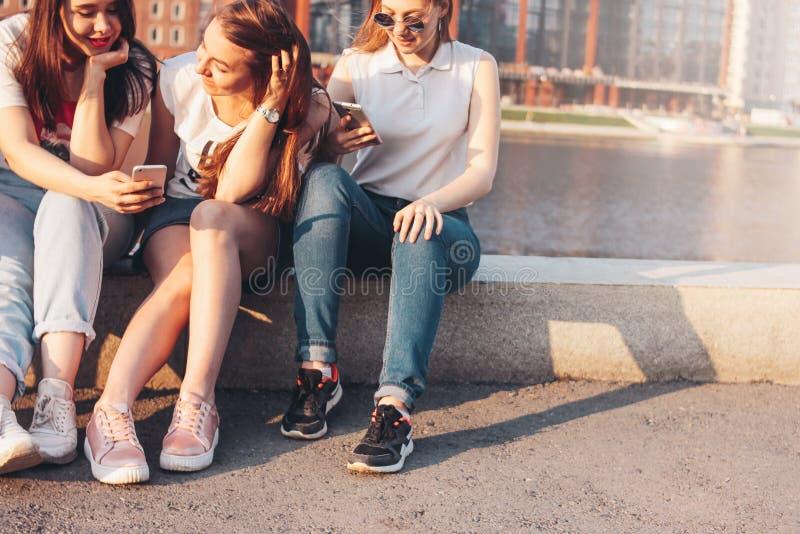 Trois jeunes étudiants heureux de vraies amies de filles employant le mobile à la rue de ville sur le fond de coucher du soleil image stock