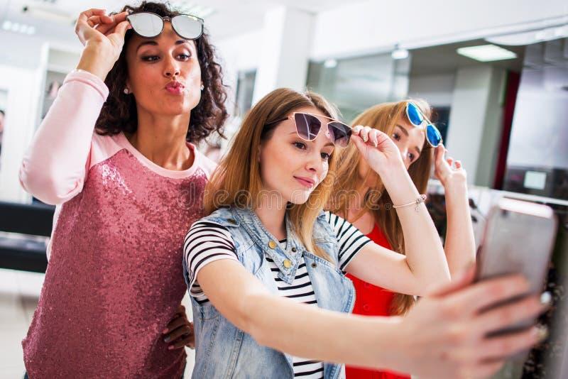 Trois jeunes amies élégantes soulevant les lunettes de soleil à la mode tout en prenant le selfie avec le smartphone dans le cent photographie stock libre de droits