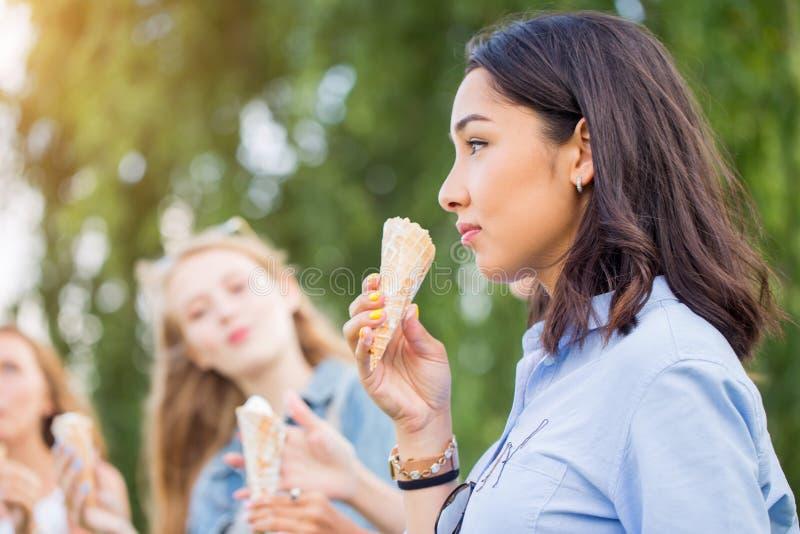 Trois jeunes amies joyeuses sur une promenade se tenant dans une rangée souriant heureusement mangent des cornets de crème glacée photographie stock