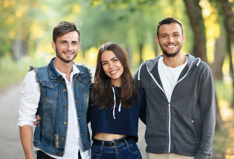 Trois jeunes amis étreignant, souriant et regardant l'appareil-photo photographie stock libre de droits