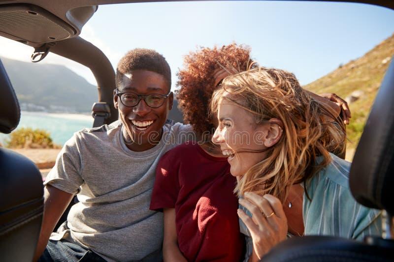 Trois jeunes amis adultes heureux s'asseyant dans une voiture ouverte par la côte, fin, taille  images stock