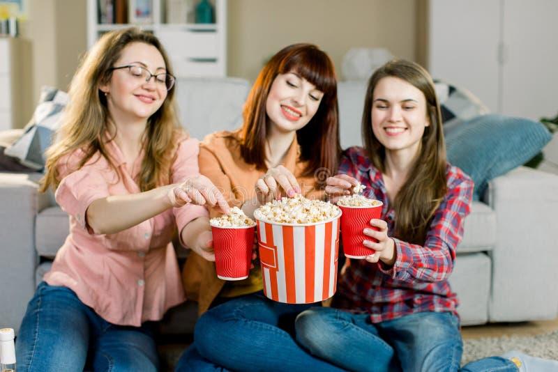 Trois jeunes amis f?minins heureux mangeant du ma?s ?clat? et s'asseyant sur le plancher pr?s du sofa ? la maison photographie stock