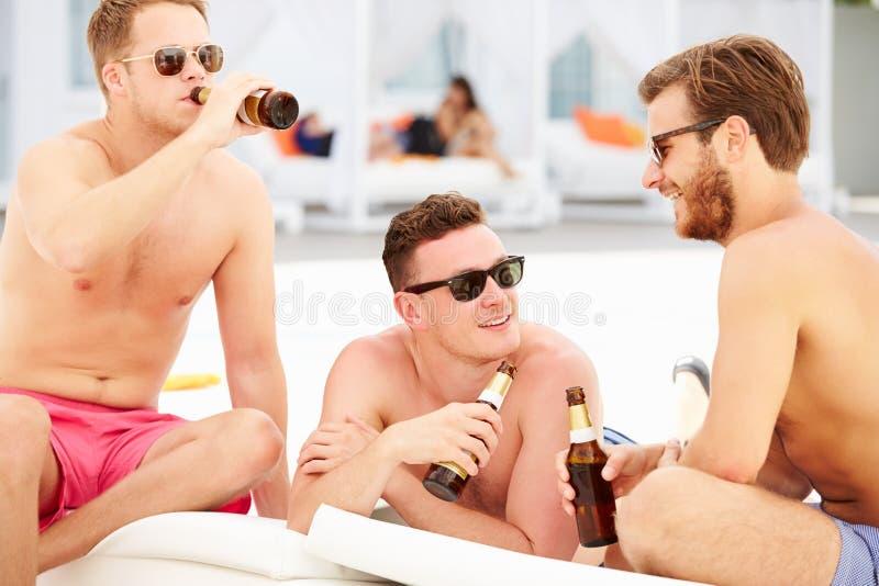 Trois jeunes amis masculins en vacances par la piscine ensemble image stock
