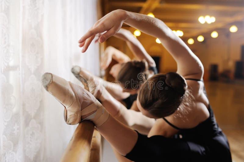 Trois jeunes ballerines mignonnes exécutent des exercices sur une machine ou un barre chorégraphique image libre de droits