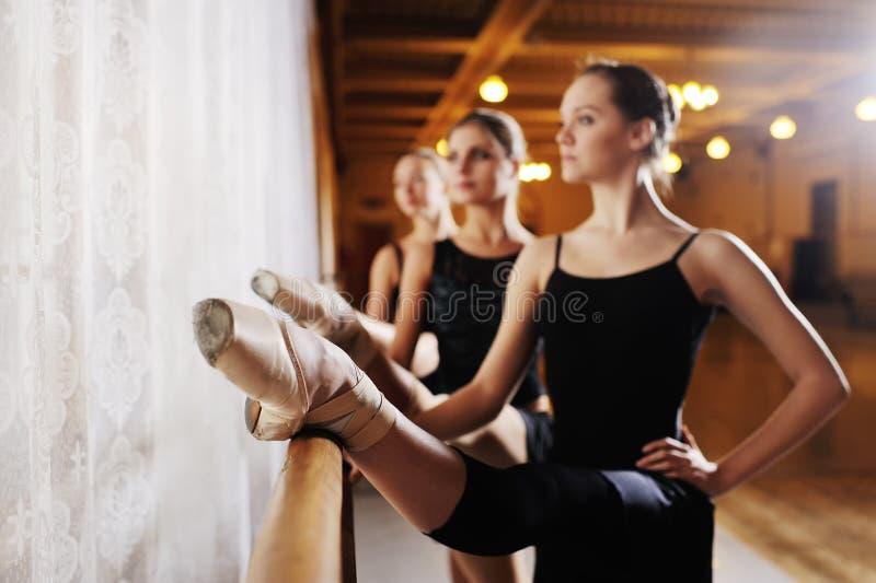 Trois jeunes ballerines mignonnes exécutent des exercices sur une machine ou un barre chorégraphique images libres de droits