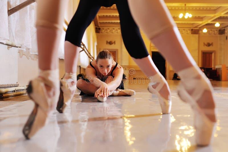 Trois jeunes ballerines mignonnes exécutent des exercices sur une machine ou un barre chorégraphique photos stock