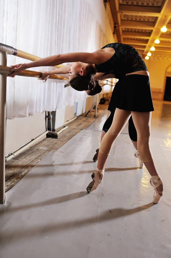 Trois jeunes ballerines mignonnes exécutent des exercices sur une machine ou un barre chorégraphique photo stock