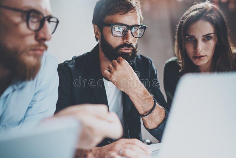 Trois jeunes collègues travaillant ensemble sur des ordinateurs portables au studio coworking moderne la nuit Verres de port d'ho photos stock