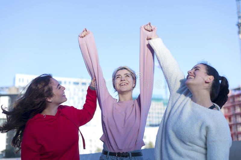 Trois jeunes femmes adultes enthousiastes heureuses dans des vêtements sport célèbrent l'extérieur de victoire photos libres de droits