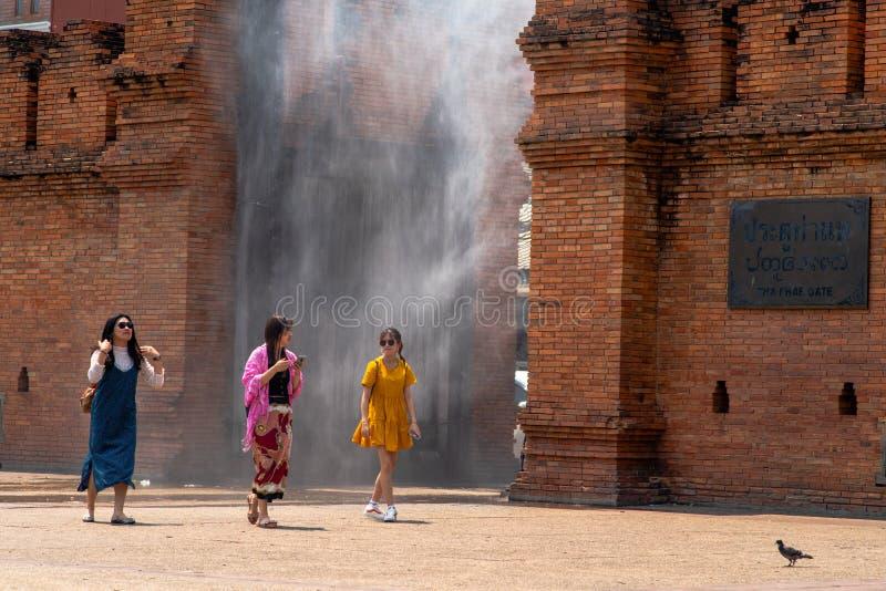 Trois jeunes femmes avec les vêtements colorés marchent par le jet d'eau installé à la porte de Thapae image stock