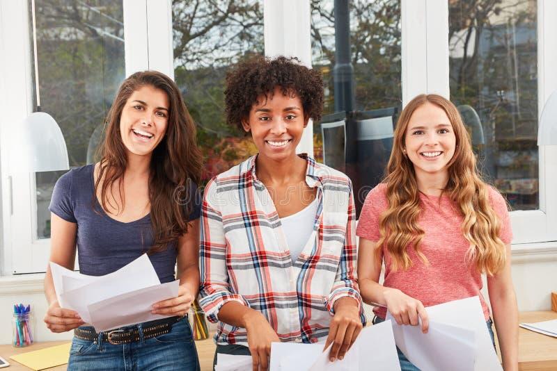 Trois jeunes femmes comme amies sourient heureusement photo stock