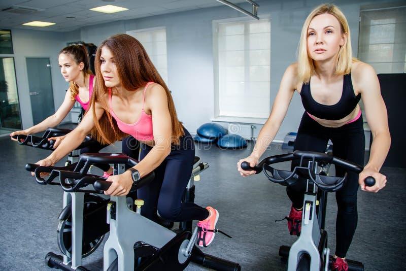 Trois jeunes femmes faisant du vélo dans le gymnase, exerçant des jambes faisant les vélos de recyclage de cardio- séance d'entra photographie stock