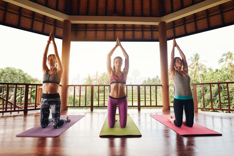 Trois jeunes femmes faisant le yoga au club de santé image stock