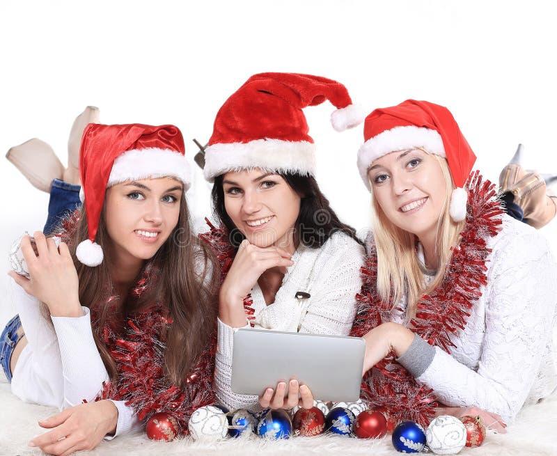 Trois jeunes femmes heureuses dans des costumes de Santa Claus regardant le comprimé photographie stock libre de droits