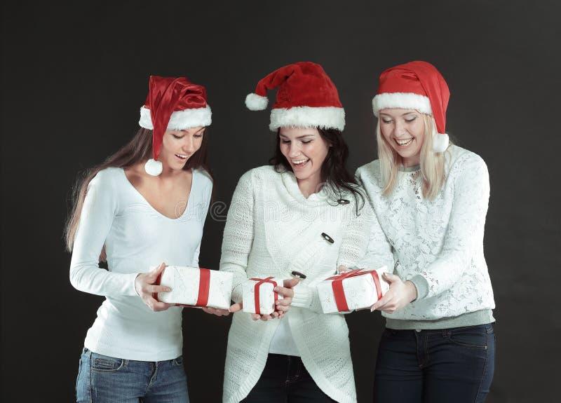 Trois jeunes femmes heureuses dans le costume de Santa Claus avec Christma photo stock