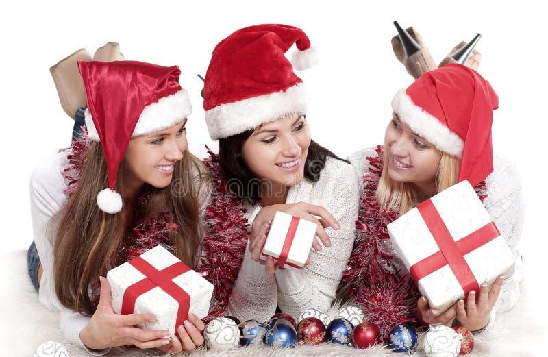 Trois jeunes femmes heureuses dans le costume de Santa Claus avec des cadeaux de Noël images libres de droits