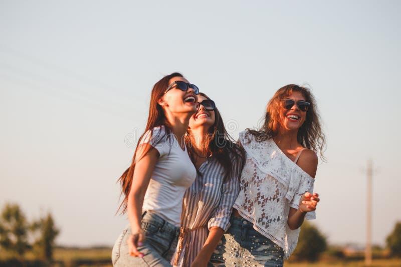 Trois jeunes femmes magnifiques dans des lunettes de soleil habillées dans les beaux vêtements sont rire extérieur un jour ensole photographie stock libre de droits