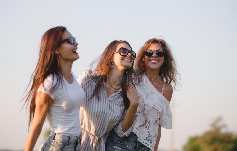 Trois jeunes femmes magnifiques dans des lunettes de soleil habillées dans les beaux vêtements sont rire extérieur un jour ensole image stock