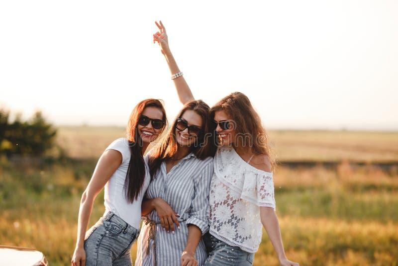Trois jeunes femmes magnifiques dans des lunettes de soleil se tiennent dans le domaine et le sourire un jour ensoleillé image stock