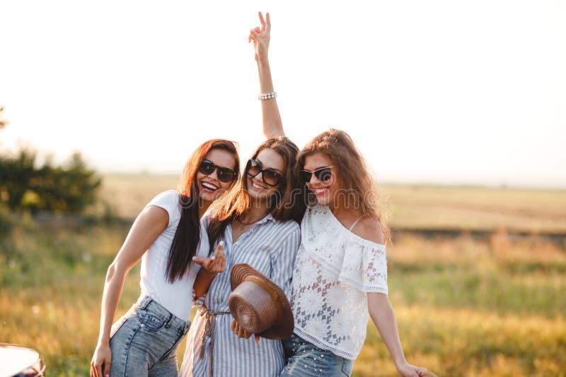 Trois jeunes femmes magnifiques dans des lunettes de soleil se tiennent dans le domaine et le sourire un jour ensoleillé photo libre de droits