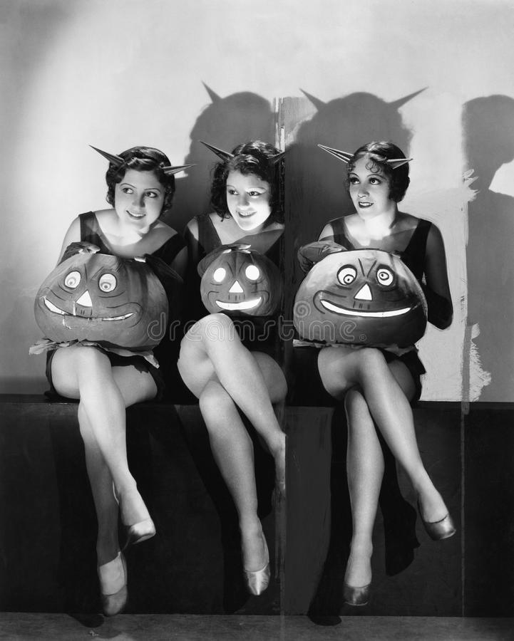 Trois jeunes femmes reposant et tenant des lanternes de Jack O sur leurs recouvrements (toutes les personnes représentées ne sont photos libres de droits