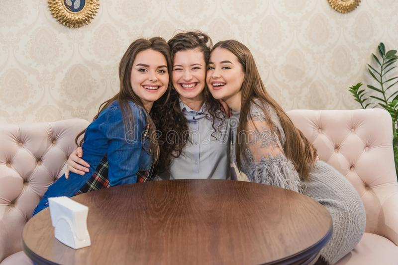 Trois jeunes femmes s'asseyant ensemble en petits cafés contre de grandes fenêtres et s'embrassant Belles jeunes filles photo stock