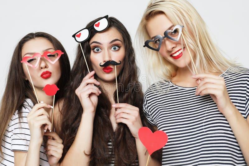 Trois jeunes femmes tenant les b?tons de papier de partie image stock