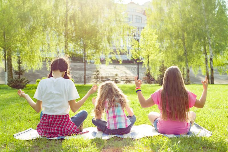 Trois jeunes filles faisant le yoga posent extérieur, yoga au coucher du soleil en parc, vue arrière image libre de droits