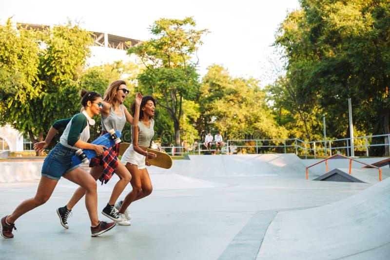 Trois jeunes filles gaies avec le fonctionnement de planches à roulettes photo libre de droits