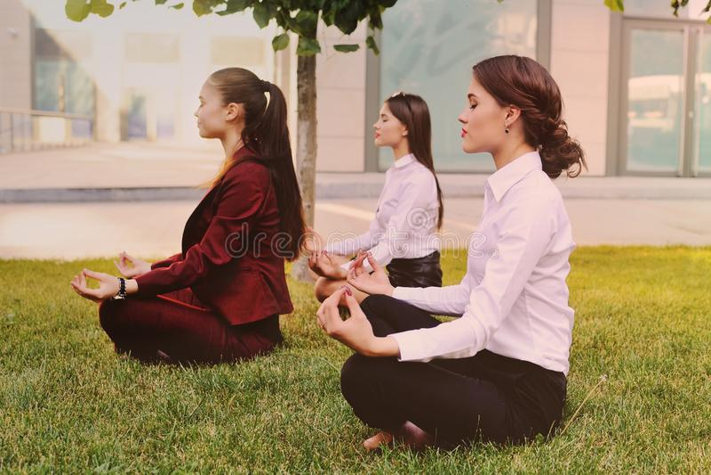 Trois jeunes filles habillées dans des vêtements de bureau pratiquent le yoga photographie stock