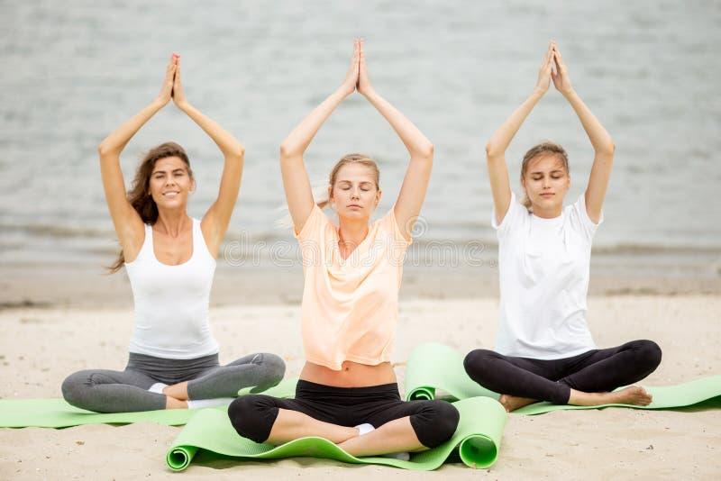 Trois jeunes filles minces s'asseyent dans un yoga pose avec des yeux de fermeture sur des tapis sur la plage sablonneuse un jour images libres de droits