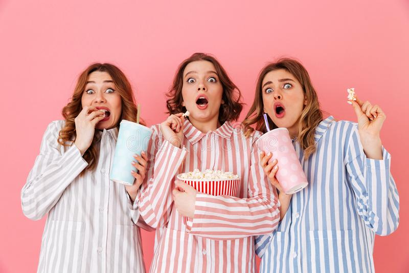 Trois jeunes filles 20s portant l'expressin rayé coloré de pyjamas photo stock