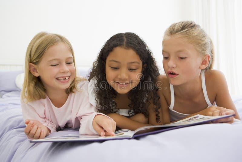 Trois jeunes filles se trouvant sur un bâti dans des leurs pyjamas photo libre de droits