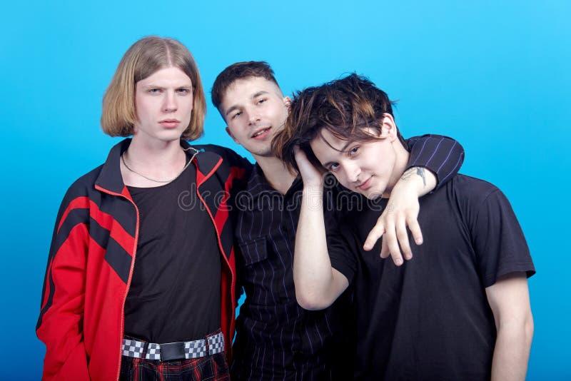 Trois jeunes hommes beaux se tiennent embrassants Relations gaies ou amitié étroite photos libres de droits