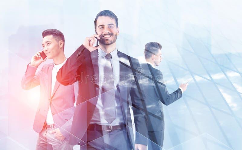 Trois jeunes hommes d'affaires à l'aide des téléphones dans la ville photos libres de droits