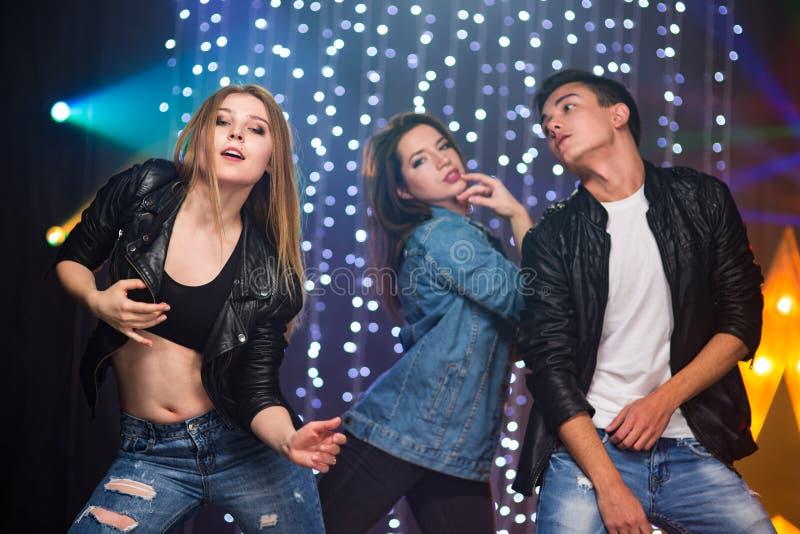 Trois jeunes hommes et deux femmes ont l'amusement dans une boîte de nuit photo stock