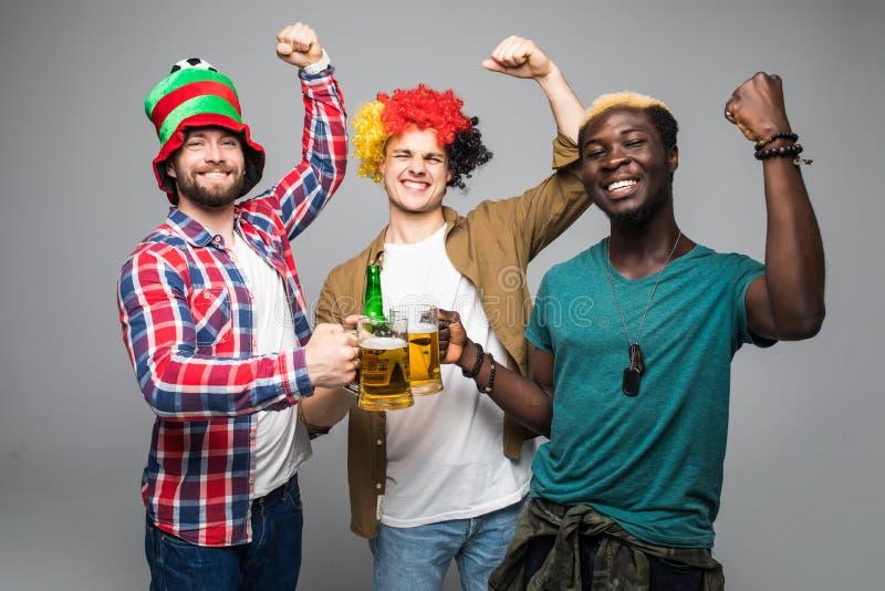 Trois jeunes hommes gais tenant la bière et célébration d'isolement au-dessus du fond blanc images libres de droits