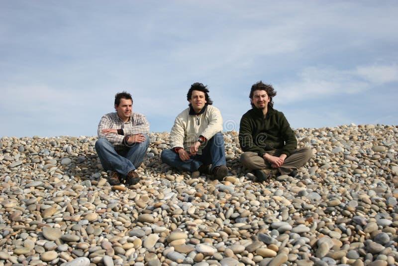 Trois jeunes hommes occasionnels à la plage photo stock