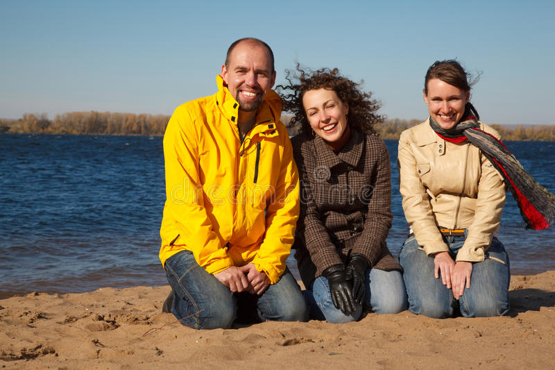 Trois jeunes hommes s'asseyent sur le côté du fleuve image stock