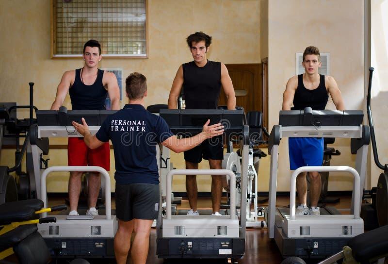 Trois jeunes hommes s'exerçant sur des tapis roulants avec l'entraîneur personnel photos stock